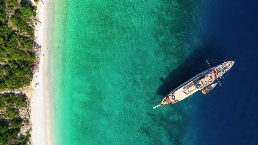 Aerial drone top down video of tropical paradise exotic island covered in pine trees with turquoise crystal clear beach in Caribbean destination