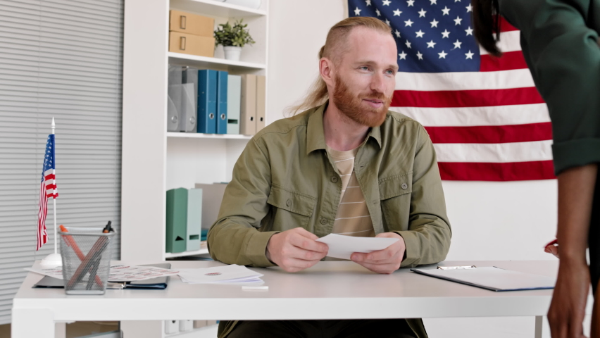 Medium shot of cheerful Caucasian man with ginger hair and beard is sitting at desk in the voting station, giving bulletins to multiethnic people coming to vote and then looking at camera