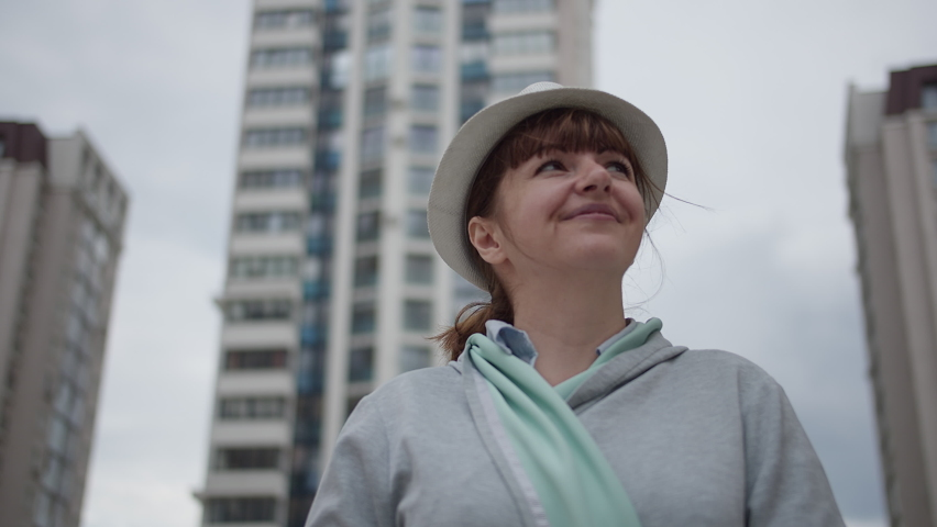 Woman in a hat stands against the background of houses and looks around | Shutterstock HD Video #1059257963