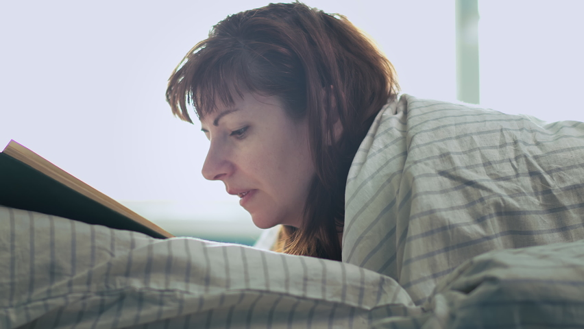 Woman lies on the bed near the window and reads a book | Shutterstock HD Video #1059257969