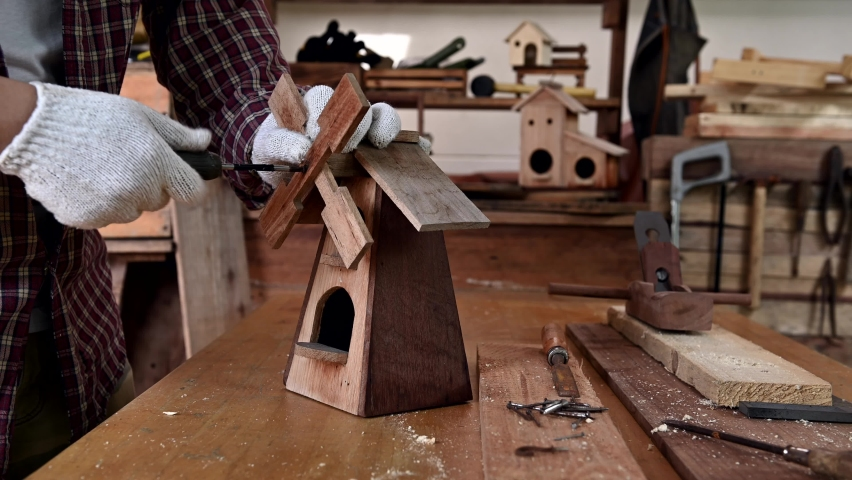 Man daily lifestyle at home. Woodworking and DIY vintage wooden bird house for garden decoration. Carpenter and craftsman workshop. | Shutterstock HD Video #1059260543