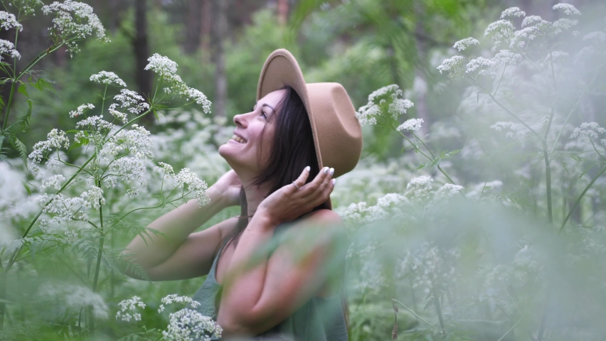 Young pretty woman in hat poses in deep forest among white flowers. | Shutterstock HD Video #1059261542