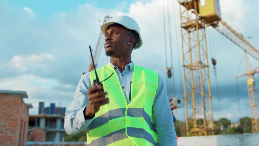African american man builder engineer worker in hard hat with use a walkie-talkie on construction helmet industrial site industry structure architecture inspector builder slow motion