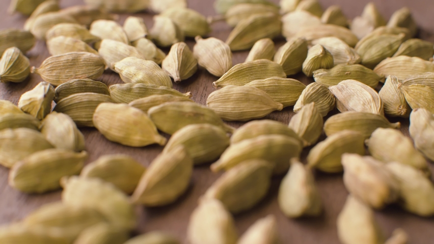 Macro shot of green dried cardamom seeds - famous aromatic spice - on the wooden background. Extreme close up, camera slowly moving on slider Royalty-Free Stock Footage #1059269339