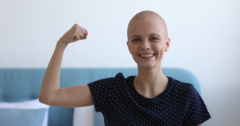 Head shot of enthusiastic bald woman smile looks at camera demonstrate biceps arm. Patient make effort stay alive struggle against oncology disease, shows strength of mind. Fights cancer concept
