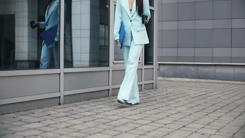 Businesswoman carrying a folder and a paper cup | Shutterstock HD Video #1059270290