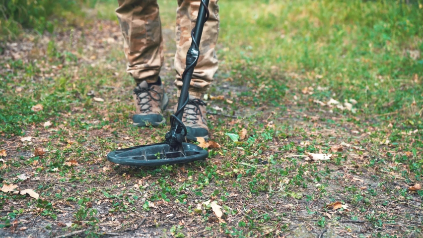 Man walks with a metal detector through the forest and looks for metal