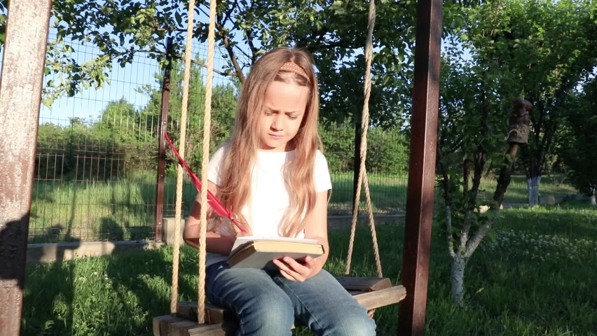 Little girl thinking and writing on nest swing. the child writes a letter with a feather pen.