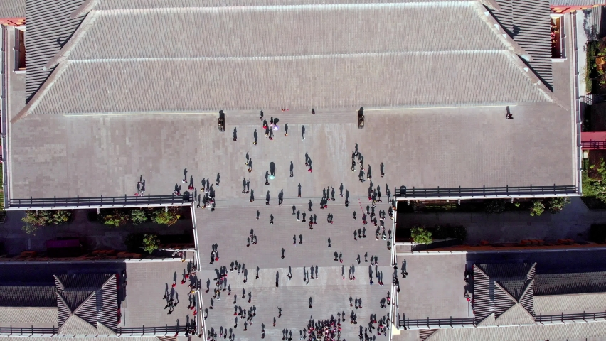 Aerial drone shot of people below and shadows on the ground during sunset at old Chinese palace. Stairs with people walking.  | Shutterstock HD Video #1059274796