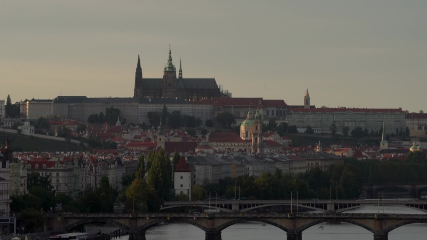 Prague Castle and the Church of St. Vitus and below it the flowing Vltava River and bridges at sunset in the center of Prague | Shutterstock HD Video #1059275009