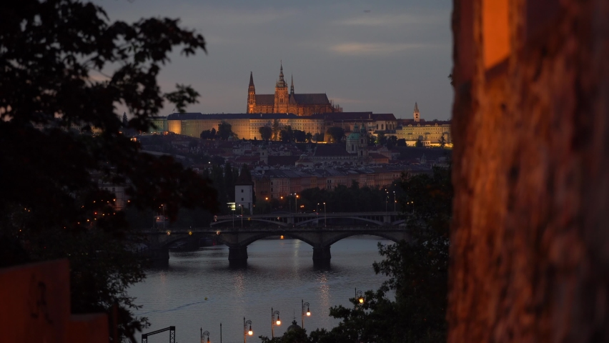 View of Prague Castle and the Church of St. Vitus and below it the flowing Vltava River and bridges at sunset in the center of Prague through the walls of the old fortress in the evening | Shutterstock HD Video #1059275051