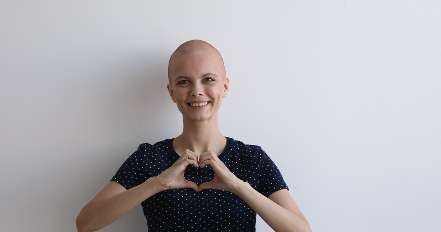 Bald young attractive female portrait on gray studio background feels healthy looks at camera showing heart symbol with hands. Cancer patient in love with life, healed woman express gratitude concept Royalty-Free Stock Footage #1059275189