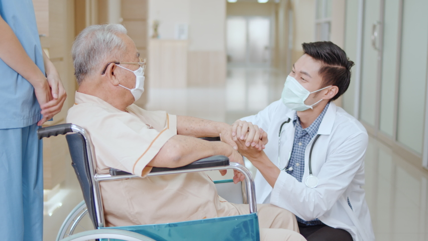 Nurse push Asian senior adult patient wheelchair in hospital hallway, young male doctor crouch down holding hand and talk to the patient with care. Medical healthcare job, or hospital business concept