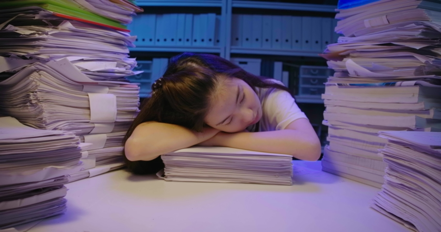 Tired young asian student woman lay down on desk cover with stack of paperwork. Alone teen girl exhausted and sleep on pile of paper sheet while studying hard overload at late night. Dolly shot | Shutterstock HD Video #1059280409