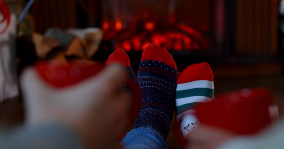 Couple Feet in Christmas Socks by the Cozy Fireplace, 4K. Man and Woman relax by warm fire, cups in hands. Winter and Christmas holidays concept. 4k | Shutterstock HD Video #1059286739
