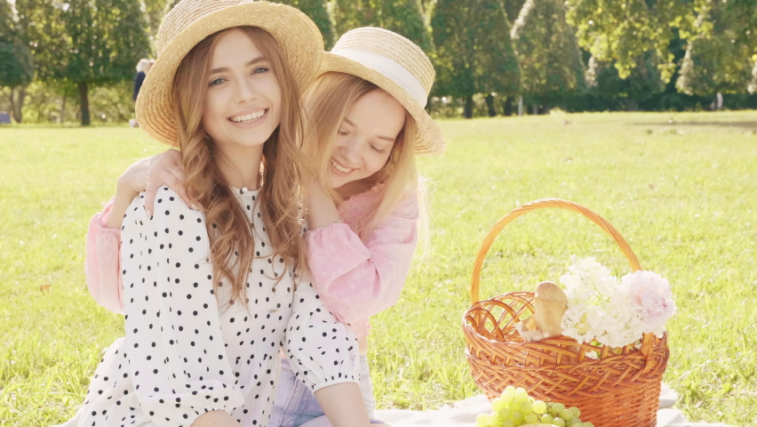 Two young beautiful hipster woman in trendy summer sundress and hats.Carefree women making picnic outside.Positive models sitting on plaid on grass,eating fruits and cheese. They looking at camera Royalty-Free Stock Footage #1059287318