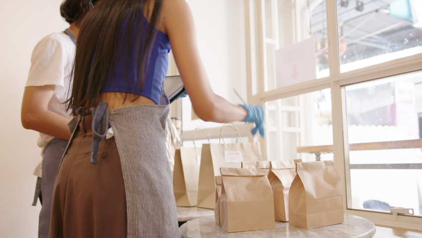 Online store, shop, restaurant or cafe preparing food take out paper bag for delivery service wearing protection gloves mask packing product ready for pick up in Small business during covid concept.