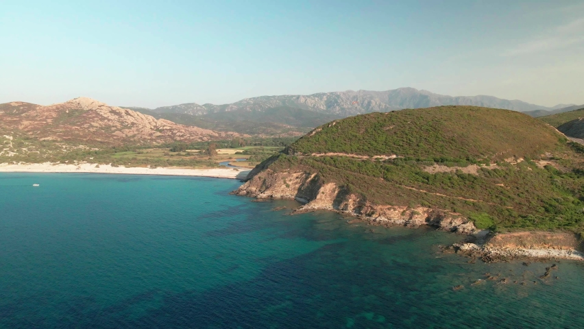 Aerial view of the rocky coastline of the Balagne region of Corsica and Ostriconi beach with a paraglider passing swooping over the hills