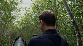 Young Attractive Man Traveler with Backpack Makes a Video on Smartphone in Green Forest. Back View. Tourist Shooting Clip for Stories to Social Media by Phone Standing on Wooden Boardwalk in Woods.