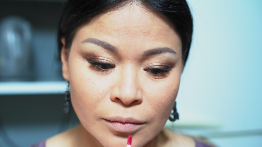 Dark-haired woman paints her lips with glitter. Middle-aged woman looks in a mirror and puts lip gloss. High quality 4k footage. | Shutterstock HD Video #1059295673