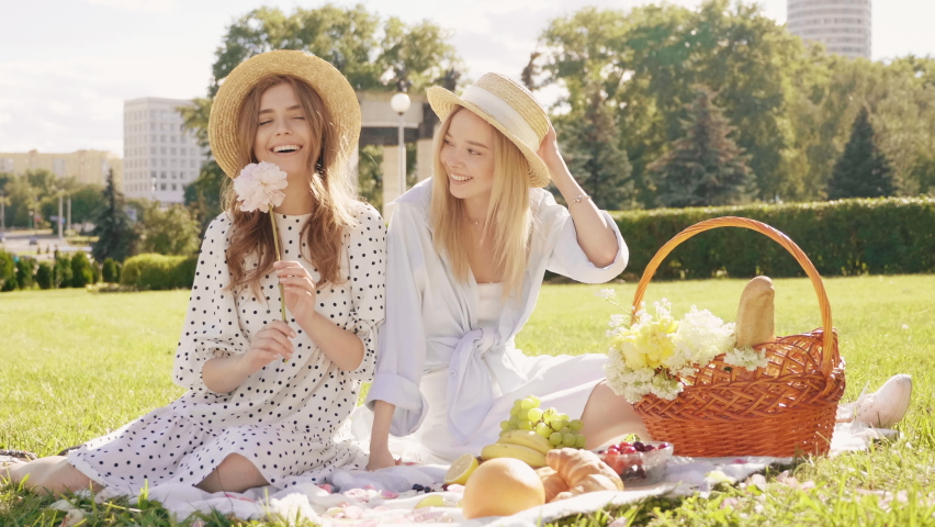 Two young beautiful hipster woman in trendy summer sundress and hats. Carefree women making picnic outside. Positive models sitting on plaid on grass, eating fruits and cheese Royalty-Free Stock Footage #1059296597