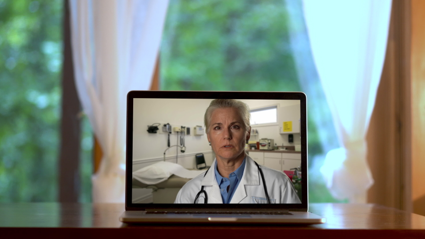 Laptop set on desk in front of french doors with a woman doctor talking about shoulder pain on computer in telemedicine set. | Shutterstock HD Video #1059296966