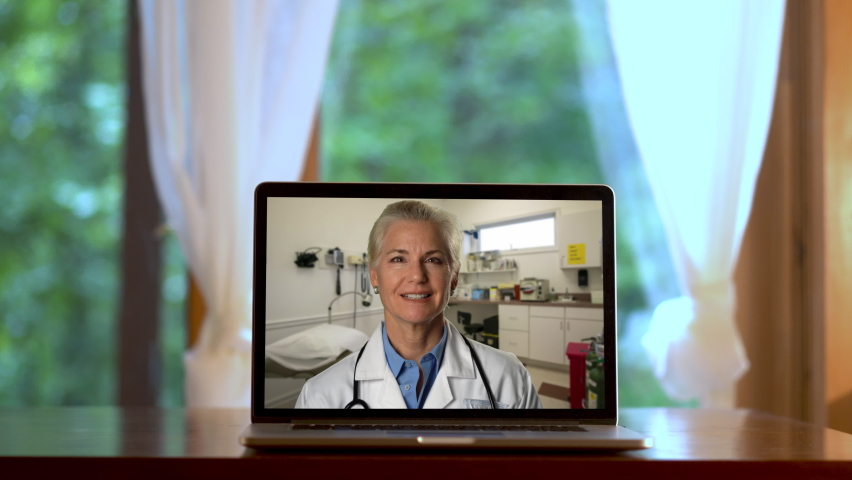 Laptop set on desk in front of french doors with a woman doctor talking computer in a telemedicine set. | Shutterstock HD Video #1059296978