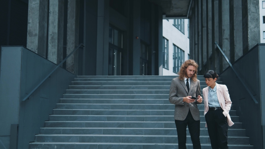 Successful couple of smart young coworkers walk outside office building, communicating and discussing apps on smartphone device, spending time outdoor. Business team. | Shutterstock HD Video #1059298352