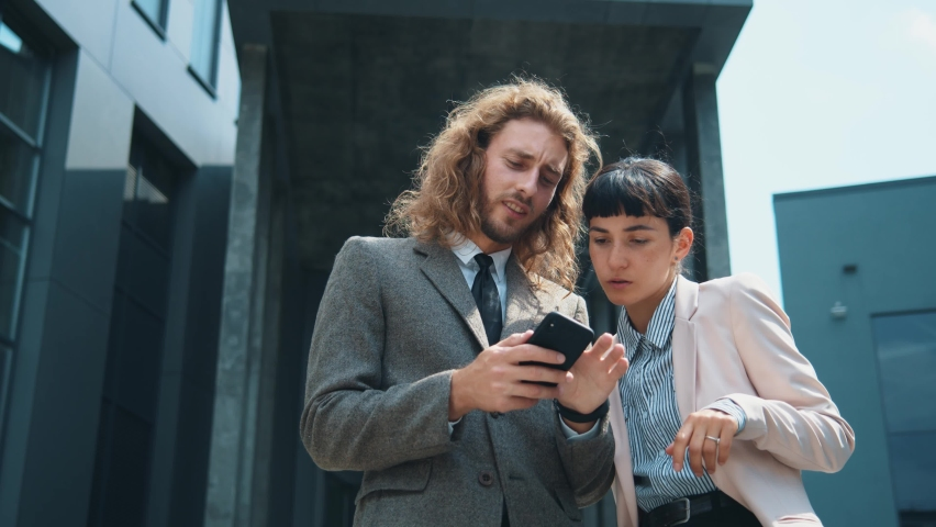 Attractive brunette busineswoman and young entrepreneur using mobile phone innovation app technology device networking outside office workspace. Business people. | Shutterstock HD Video #1059298367