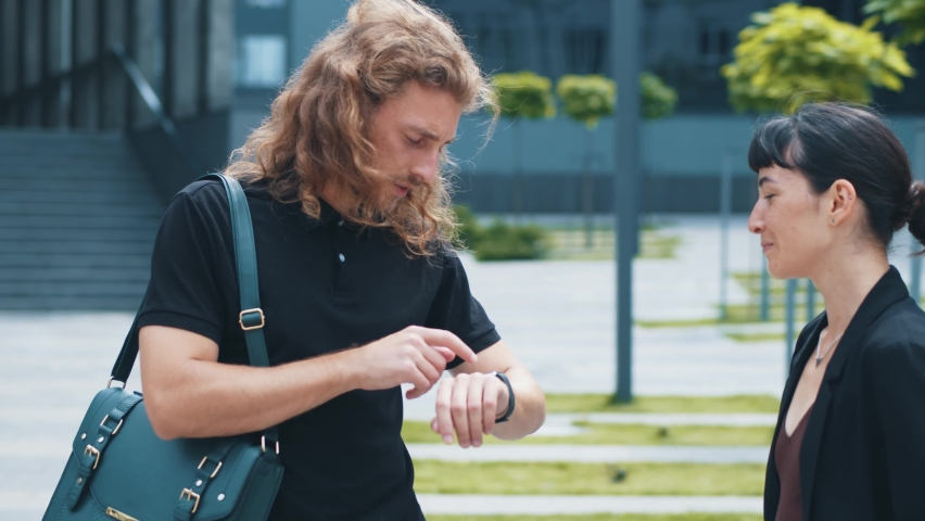 Handsome cute caucasian couple of coworkers talking on business and handsome man with curly hair laughing smiling using his smartwatch. Communication. Two people. Business. | Shutterstock HD Video #1059298376