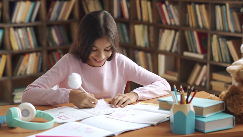 Happy smiling indian latin preteen school girl pupil studying at home sitting at desk. Smart cute hispanic kid primary school student writing in exercise book doing homework, learning at table. Royalty-Free Stock Footage #1059300785