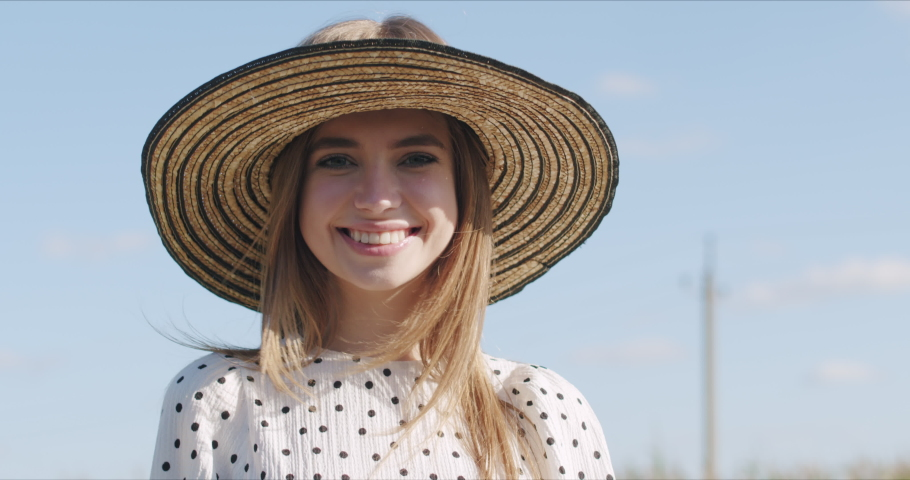Fashion portrait sweet young woman having fun with lollipop over blue sky. Pretty girl wearing dress and hat smiling. 4k raw video footage