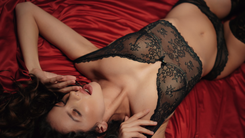 Closeup pretty woman touching lips with finger on red silk sheet. Naked girl stroking neck on satin fabric. Sexy brunette woman in lace lingerie posing on bed. Sex desire concept