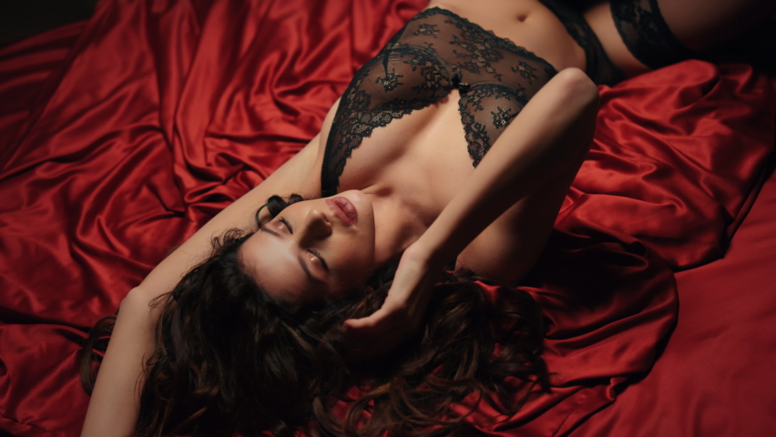 Top view seductive woman touching face skin on red silk bed. Closeup sexy girl with long curly hair lying on red satin sheets in lace lingerie.. Erotic model girl posing and dreaming about sex on bed.