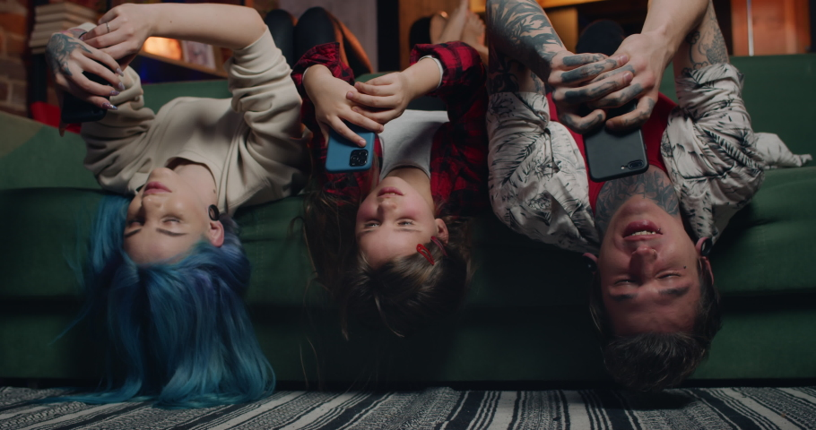 Cheerful family lying on sofa upside down and using smartphones. Modern mother, father and their kid chatting in social networks while spending time. People with tattoos and piercing. | Shutterstock HD Video #1059310997