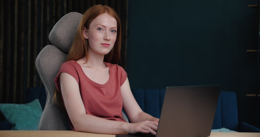 Portrait of cute Red-Haired Female Freelancer, Student is looking at the Camera. Ginger is sitting at cozy Home Office, working on Laptop, enjoying her Job. Working Indoor, Distant Education. Royalty-Free Stock Footage #1059311291