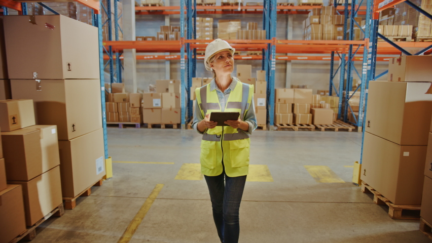 Professional Female Worker Wearing Hard Hat Uses Digital Tablet Checks Inventory Walks in the Retail Warehouse full of Shelves with Goods. Working in Logistics, Distribution Center. Following Shot Royalty-Free Stock Footage #1059312620