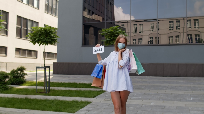 Young stylish model girl in protective mask with shopping bags showing Sale word inscription text, looking satisfied with low prices purchases during coronavirus, covid-19 pandemic. 6k downscale | Shutterstock HD Video #1059328676