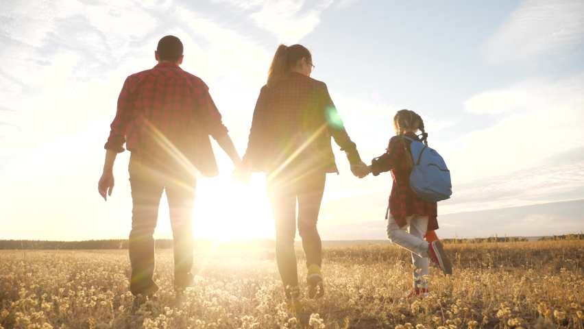 Happy family walking in the park. friendly family kid dream concept. mom dad and child kid walk in the park on green grass outdoors lifestyle. happy family with their backs walking in the park | Shutterstock HD Video #1059339359