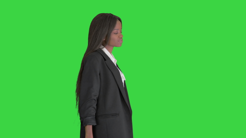 Confident smiling african american businesswoman putting hands in her pockets on a Green Screen, Chroma Key. | Shutterstock HD Video #1059356795
