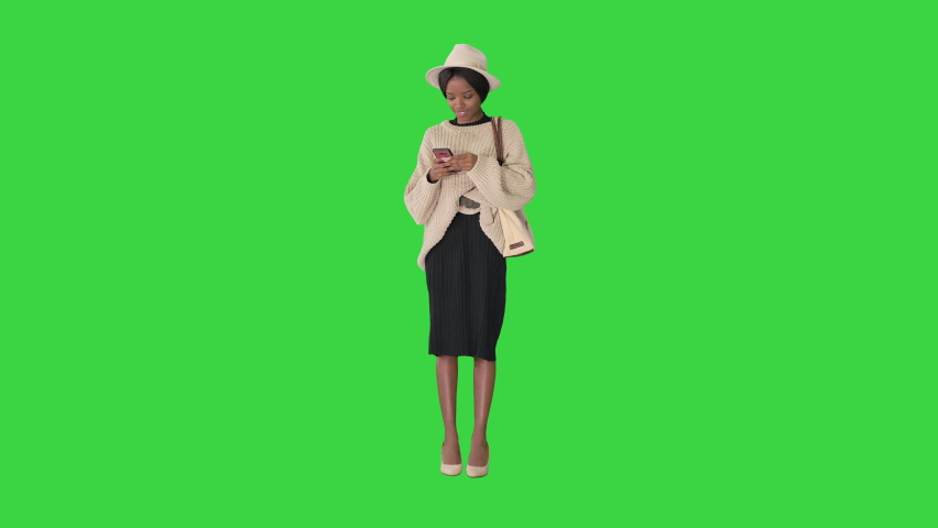 Pretty african american woman in knitted sweater and white hat answering her phone on a Green Screen, Chroma Key. | Shutterstock HD Video #1059356804