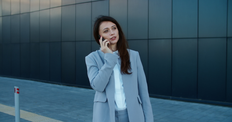 Smiling Business woman in a business suit stands near a modern building and talks on a mobile phone. Female portrait. High quality 4k footage | Shutterstock HD Video #1059357266