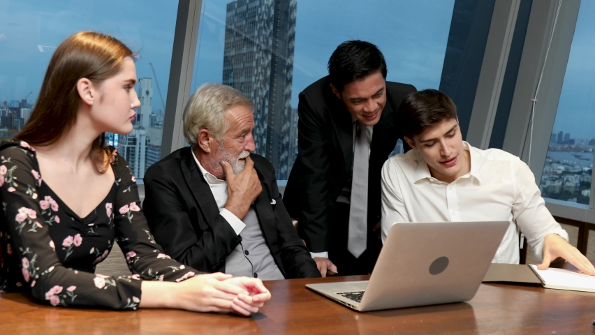 Motivated young team leader explaining company development strategy to smiling diverse colleagues. Happy multiracial business people enjoying working together at office. Concept of overwork. | Shutterstock HD Video #1059357518