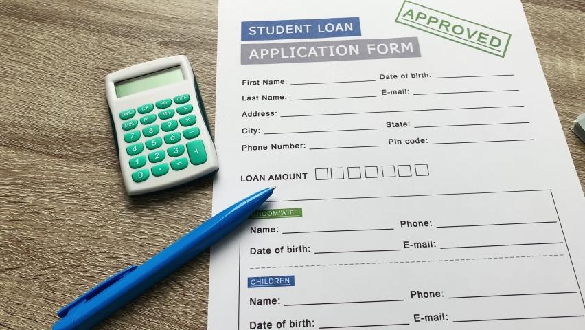 Student loan application form on wood table. | Shutterstock HD Video #1059357611