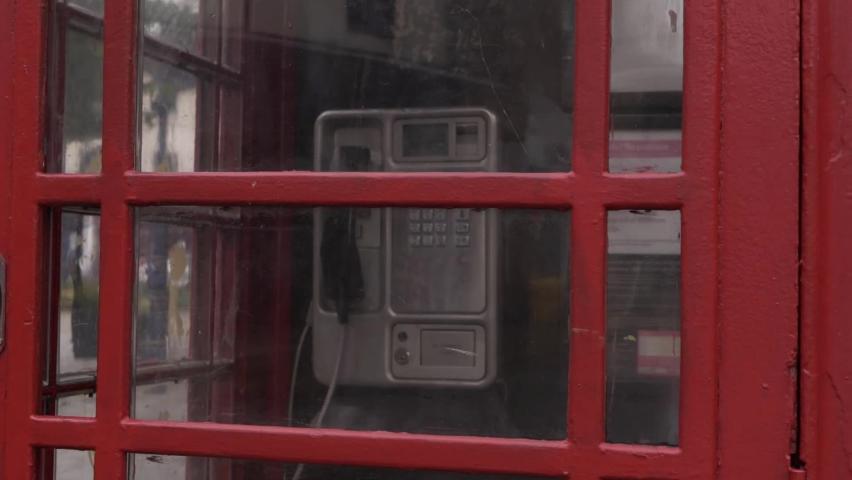 Red phone box in British city medium panning shot | Shutterstock HD Video #1059358034