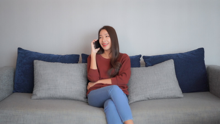 Attractive young woman talking on a mobile phone while sitting on a couch in her living room. | Shutterstock HD Video #1059358160