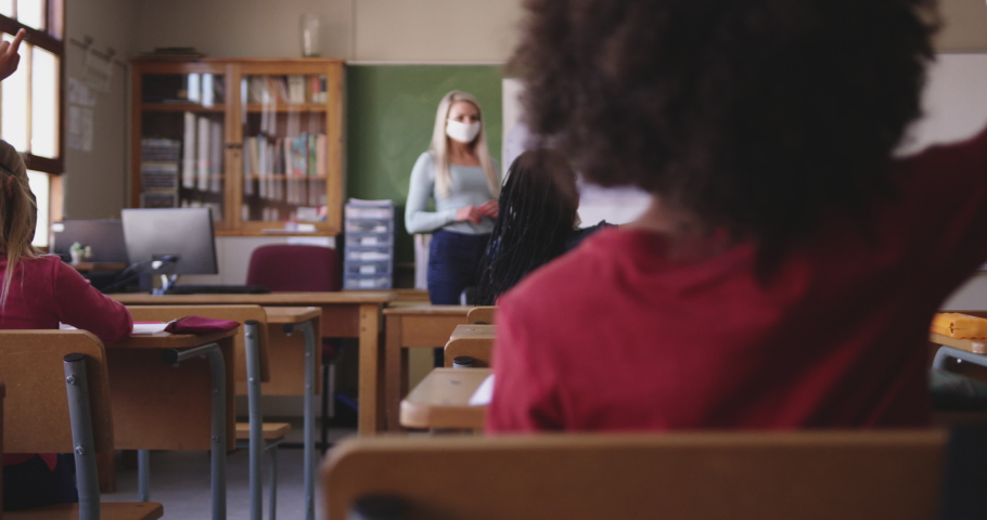 Group of multi ethnic kids in the classroom at school, raising hands, wearing masks. Primary education social distancing health safety during Covid19 Coronavirus pandemic in slow motion. Royalty-Free Stock Footage #1059379418