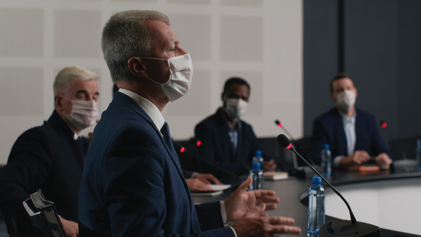 Political speaker talks at meeting room of business center. Man in suit and mask explains coronavirus epidemic. 2019-ncov conference indoors of convention hall. Expert group works at official event