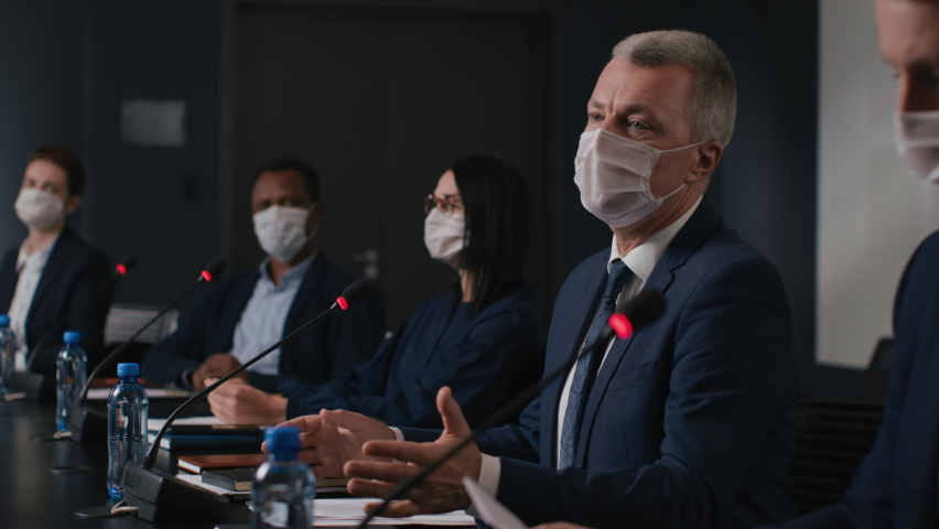 Speech of political speaker at meeting room of business forum. Man in suit and mask discusses covid-19 pandemic. 2019-ncov conference indoors of convention hall. Expert group works at official event Royalty-Free Stock Footage #1059381563