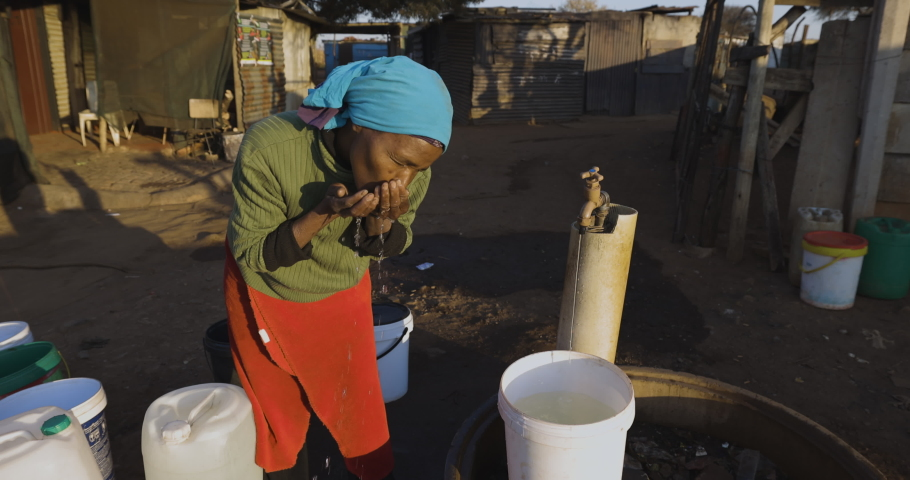 Face of poverty.  Poor Black African woman with no access to running water, drinks water while filling up buckets at a central tap to take to her house in an informal settlement (squatter camp)